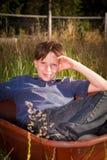 Menino novo ocasional em um carrinho de mão Fotos de Stock Royalty Free