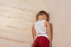 Menino novo pequeno que enfrenta a parede de madeira imagem de stock