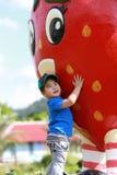 Menino novo que abraça uma boneca grande da morango Imagem de Stock