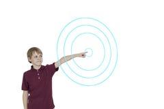 Menino novo que aponta aos círculos concêntricos digitalmente projetados sobre o fundo branco Foto de Stock