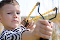 Menino novo que aponta o tiro de estilingue na câmera Fotografia de Stock Royalty Free