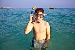 Menino novo que aprecia snorkeling no mar Fotos de Stock Royalty Free