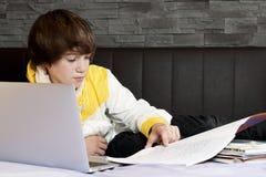 Menino novo que aprende com um caderno e os livros Imagem de Stock