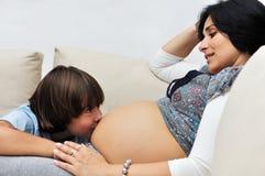 Menino novo que beija a mulher gravida Fotografia de Stock