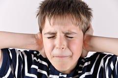 Menino novo que cobre suas orelhas com as mãos Fotografia de Stock Royalty Free