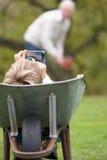 Menino novo que coloca o Wheelbarrow usando o telefone móvel Imagem de Stock Royalty Free