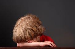 Menino novo que coloca sua cabeça em seus braços Imagem de Stock