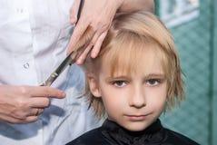 Menino novo que começ um corte de cabelo Imagem de Stock