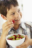 Menino novo que come a bacia de fruta fresca imagens de stock royalty free