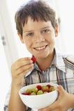 Menino novo que come a bacia de fruta fresca foto de stock