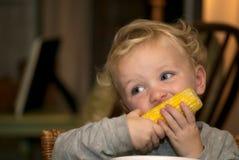 Menino novo que come a espiga de milho foto de stock
