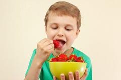 Menino novo que come morangos frescas da bacia Fotografia de Stock Royalty Free
