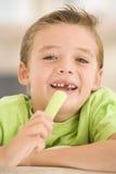 Menino novo que come o aipo na sala de visitas Imagens de Stock Royalty Free