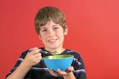 Menino novo que come o cereal fotografia de stock