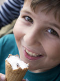 Menino novo que come o gelado Fotos de Stock Royalty Free