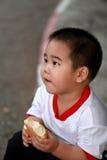Menino novo que come o pão Imagem de Stock Royalty Free