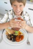 Menino novo que come o pequeno almoço fritado insalubre Fotografia de Stock Royalty Free