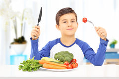 Menino novo que come a refeição saudável assentada na tabela Imagens de Stock Royalty Free
