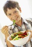 Menino novo que come uma salada saudável imagem de stock
