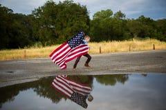 Menino novo que corre com uma bandeira americana, liberdade fotos de stock