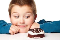 Menino novo que decide comer uma sobremesa Fotos de Stock