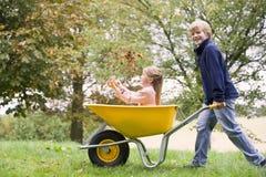 Menino novo que empurra a menina no wheelbarrow Fotos de Stock Royalty Free