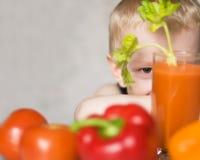 Menino novo que esconde entre vegetais foto de stock royalty free