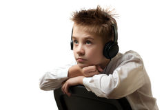 Menino novo que escuta os telefones principais Foto de Stock