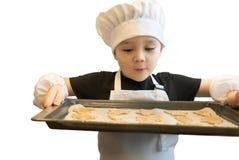 Menino novo que está com bandeja do cozimento completamente de cookies do pão-de-espécie, cutted com a ajuda dos moldes diferente Imagens de Stock