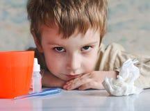 Menino novo que está com a gripe Imagem de Stock