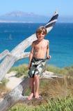 Menino novo que está na árvore em uma praia ensolarada Fotografia de Stock Royalty Free