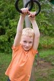 Menino novo que exercita em anéis da ginástica fotos de stock royalty free