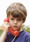 Menino novo que fala no telefone Imagens de Stock