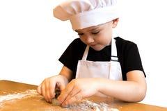 Menino novo que faz o pão-de-espécie Caçoe cookies do corte com moldes, cozimento ele para a tabela do Natal Isolado no branco Fotos de Stock