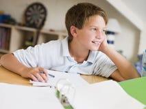Menino novo que faz trabalhos de casa em seu quarto Foto de Stock