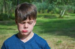 Menino novo que faz uma cara triste fora imagens de stock