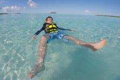 Menino novo que flutua no revestimento de vida na água azul claro com o navio de cruzeiros no fundo imagem de stock