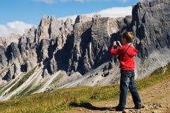 Menino novo que fotografa montanhas Fotos de Stock Royalty Free