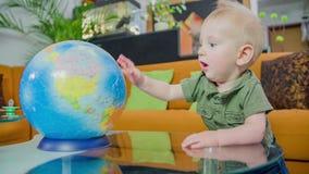 Menino novo que gira o globo vídeos de arquivo