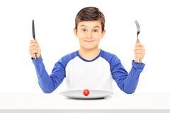 Menino novo que guarda a forquilha e a faca com o tomate de cereja na frente de Imagens de Stock