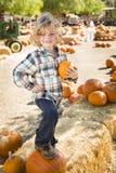 Menino novo que guarda sua abóbora em um remendo da abóbora Fotografia de Stock