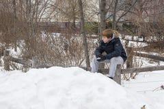 Menino novo que guarda uma bola de neve fotografia de stock