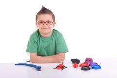Menino novo que joga com argila de modelagem Foto de Stock Royalty Free
