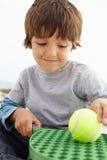 Menino novo que joga com bastão e esfera Fotografia de Stock Royalty Free