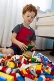 Menino novo que joga com blocos de apartamentos Fotos de Stock Royalty Free