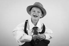 Menino novo que joga com câmera velha para ser um fotógrafo Imagem de Stock