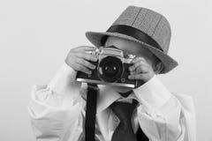 Menino novo que joga com câmera velha para ser um fotógrafo Fotografia de Stock Royalty Free