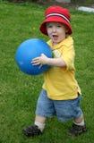 Menino novo que joga com esfera Imagens de Stock Royalty Free