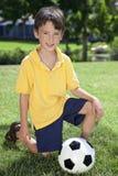 Menino novo que joga com a esfera do futebol ou de futebol Fotografia de Stock