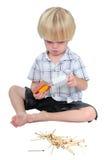 Menino novo que joga com fósforos em um fundo branco Imagens de Stock